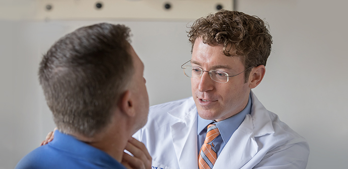 SLUCare otolaryngologist Dr. Greg Ward works with a cancer patient