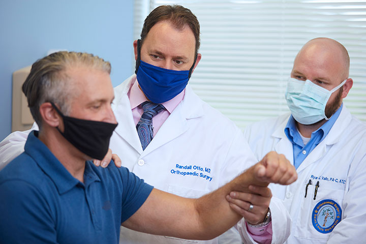 SLUCare orthopedic specialists Dr. Randall Otto and Ryan Vallo examine a patient's shoulder