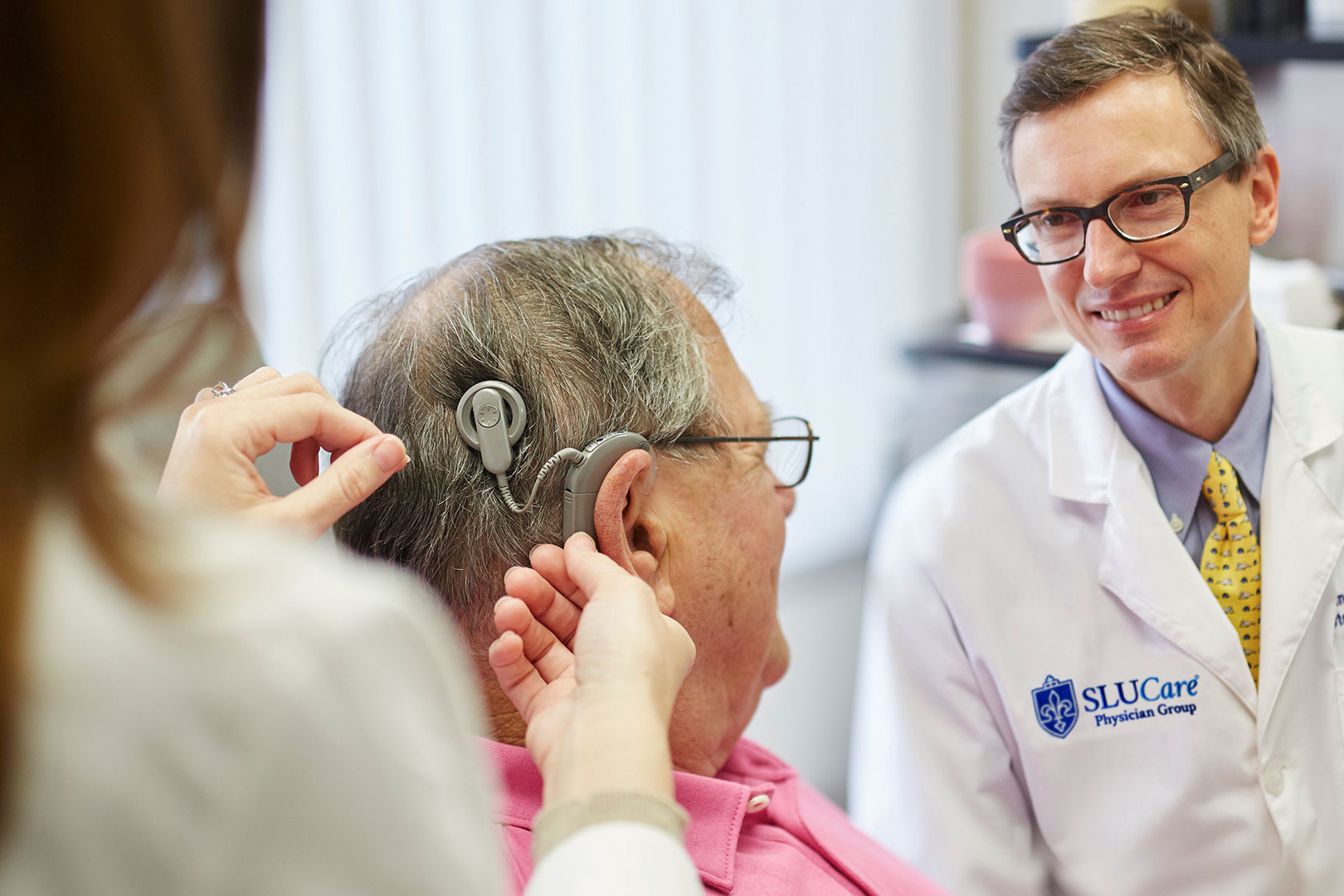 Adjusting patient's hearing aid.